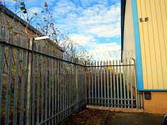 Palisade fence enhancements - extra lower horizontal support rail and additional razor wire on top