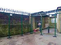 Green powder coated V-Beam mesh panel fencing fitted at a special needs school - fence incorporates additional fence posts# mesh clamp bars instead of the usual fence clips and a top row of rotating spikes