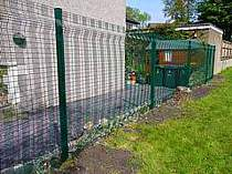 Green powder coated mesh panel fencing - mesh panels secured with mesh clamp bars to provide additional security