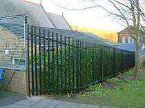 Black powder coated palisade fencing with a raked fence panel