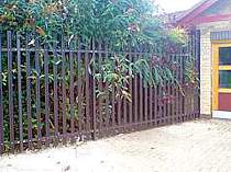 Brown powder coated palisade fencing incorporating a raked end panel