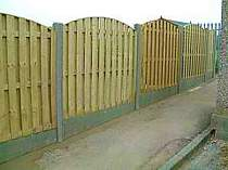 Wood panel fence using concrete slotted posts and gravel boards