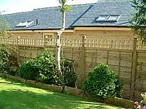 Heavy duty wood panel fence with additional top trellis panel
